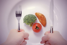 a skinny man with his hands on the plate with food